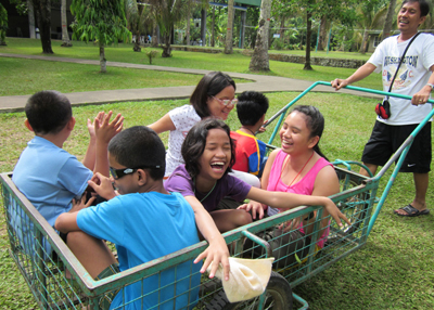 Group of blind children riding in a cart at outdoor camp