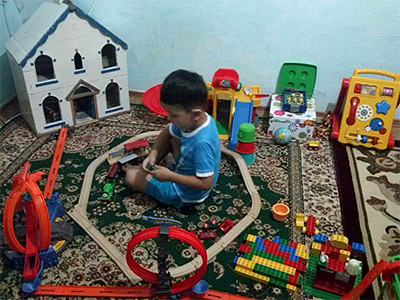 blind child playing, surrounded by tactile toys